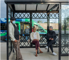 Three people waiting at a bus shelter. Two are sitting, one is standing. There is a COTA Plus vehicle in the background.